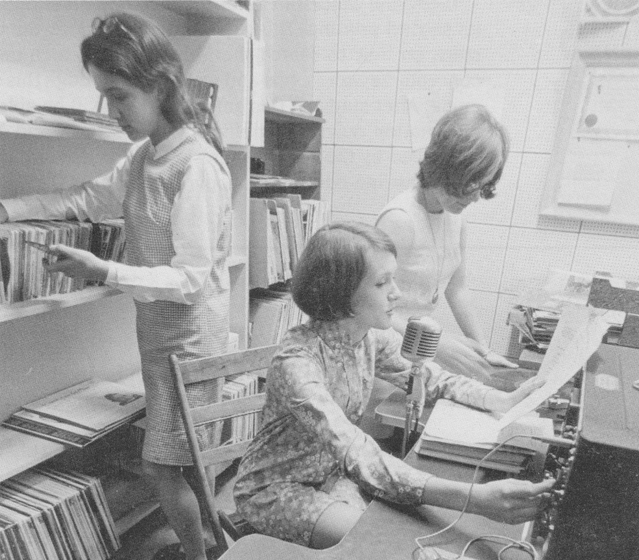 Aumack, at the microphone, DJs for Wilson radio station as her roommate Susan Burich Redding '71 looks through records.